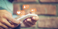 mobile in hands with social icons rising from screen